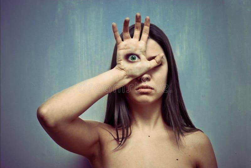 Mulher nova com olho em uma palma imagem de stock royalty free