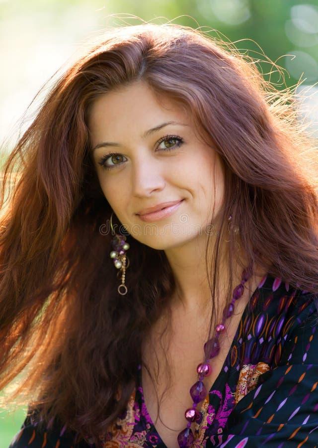Mulher nova com os grânulos roxos no parque do verão fotografia de stock