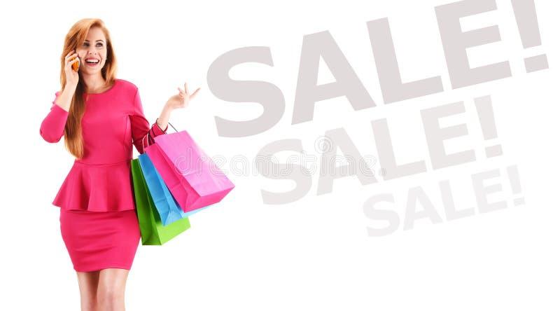Mulher nova com os sacos de compra isolados no branco fotografia de stock