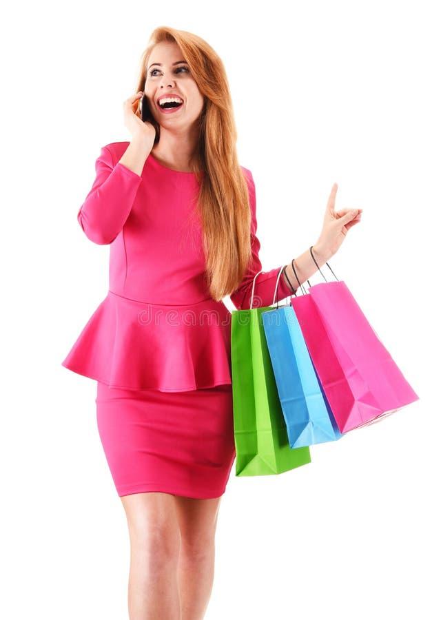 Mulher nova com os sacos de compra isolados no branco imagem de stock