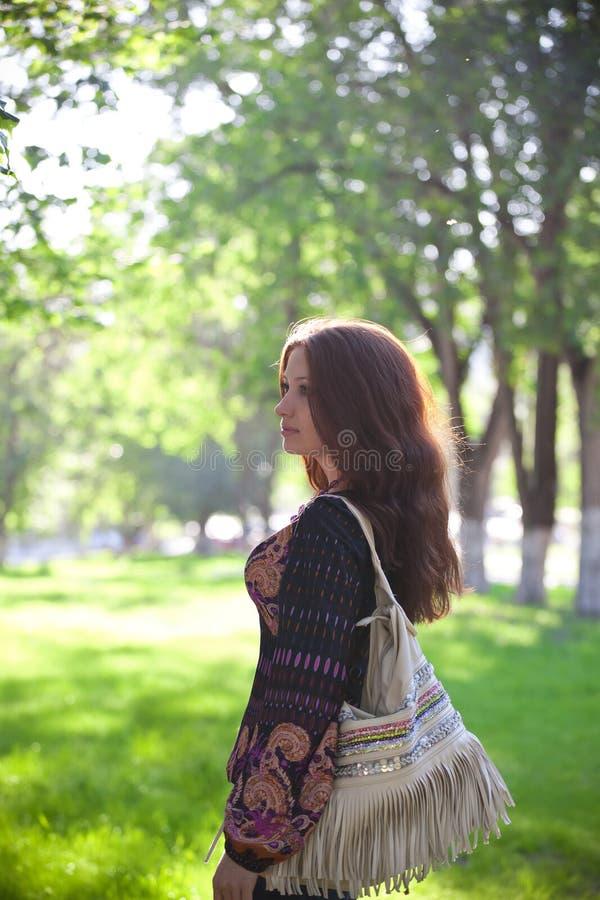 Mulher nova com saco que anda no parque do verão foto de stock royalty free