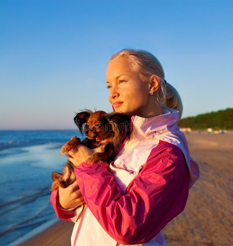 Mulher nova com seu cão em uma praia fotos de stock