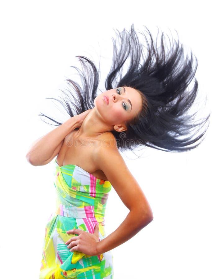 Mulher nova com seu cabelo que funde e que sorri, dentro imagens de stock royalty free