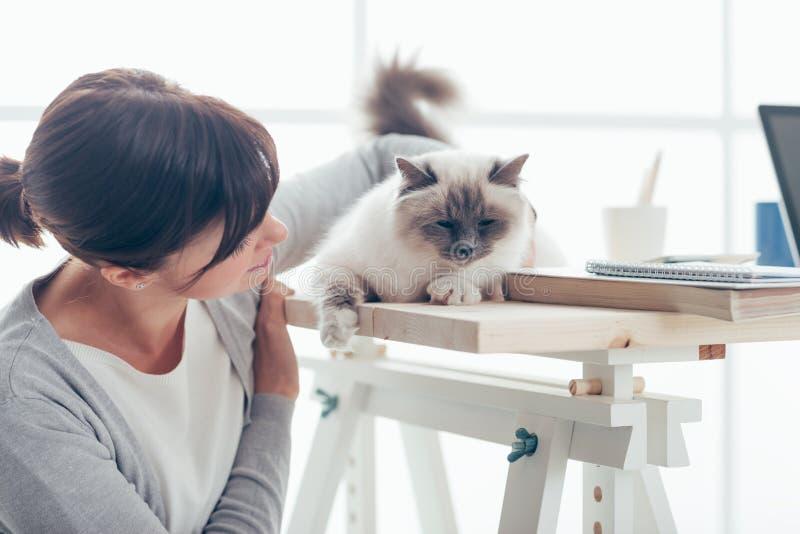 Mulher nova com seu gato cinzento encantador fotografia de stock