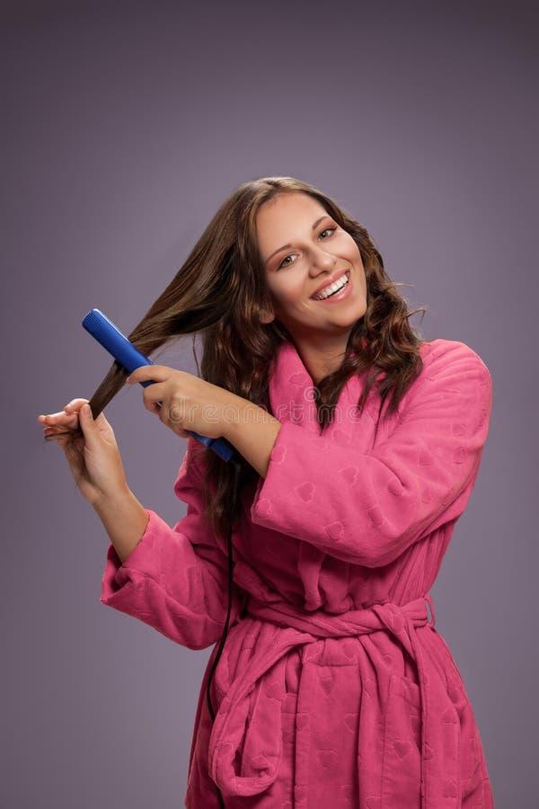 Mulher nova com straightener do cabelo fotografia de stock