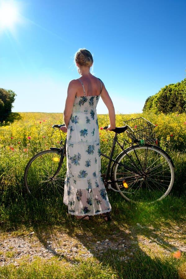 Mulher nova com uma bicicleta fotos de stock
