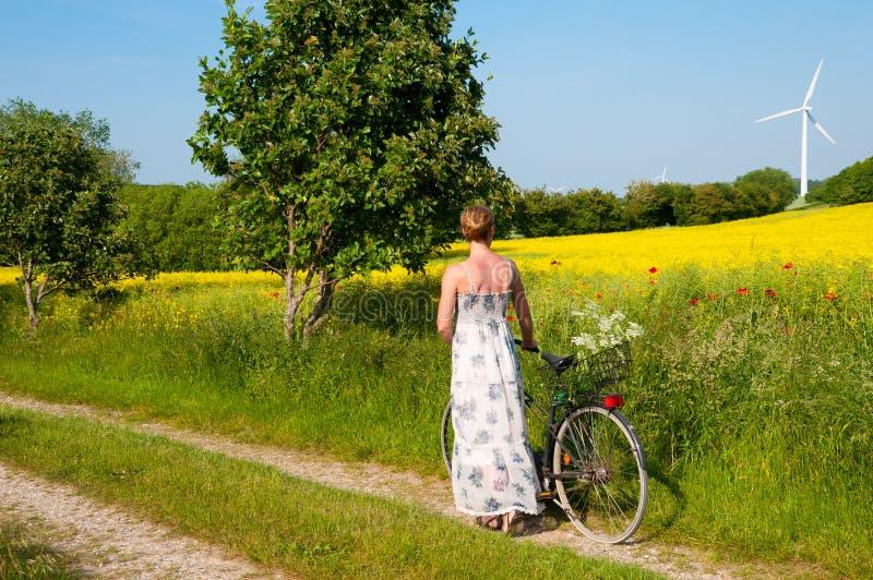 Mulher nova com uma bicicleta imagens de stock