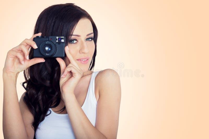 Mulher nova com uma câmera do vintage fundo do pantone fotos de stock