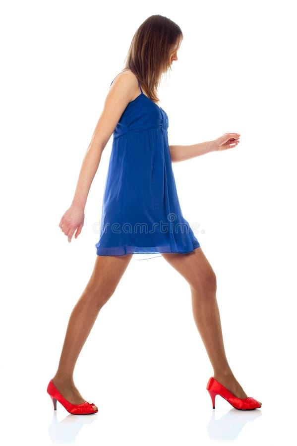Mulher nova com vestido azul e as sapatas vermelhas fotografia de stock royalty free