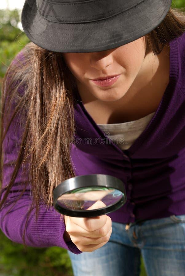 Mulher nova com vista do vidro e do chapéu do magnifier imagens de stock