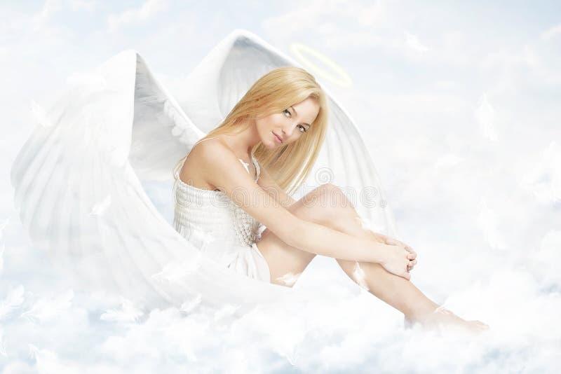 Mulher nova como o anjo que senta-se em nuvens fotos de stock