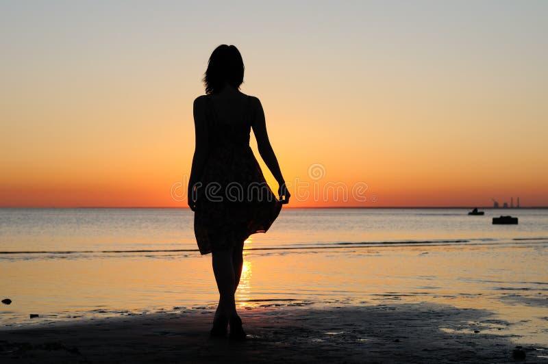 Mulher nova como a silhueta pelo mar fotos de stock royalty free