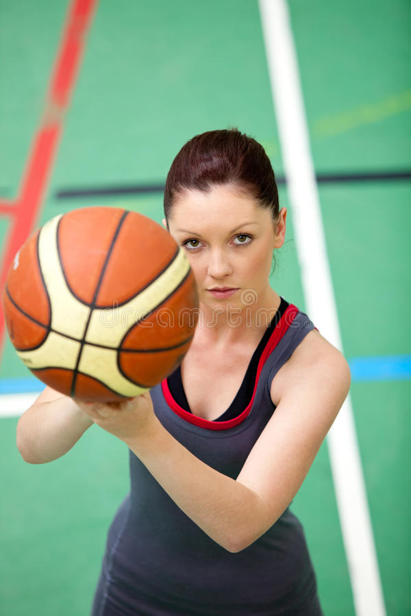 Mulher nova concentrada que joga o basquetebol fotos de stock royalty free