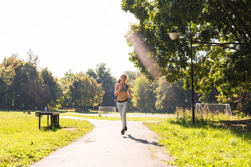 Mulher nova da aptidão do estilo de vida saudável que corre fora imagens de stock