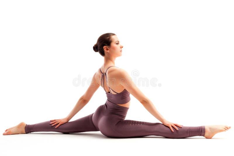 A mulher nova da aptidão faz o assento da separação do pé no assoalho branco fotografia de stock royalty free