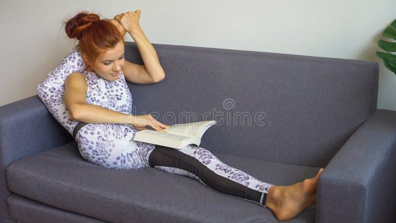 a mulher nova da aptidão no sportswear que faz a ioga que estica o pé pôs sobre seu pescoço quando livro de leitura no sofá na sa fotografia de stock royalty free