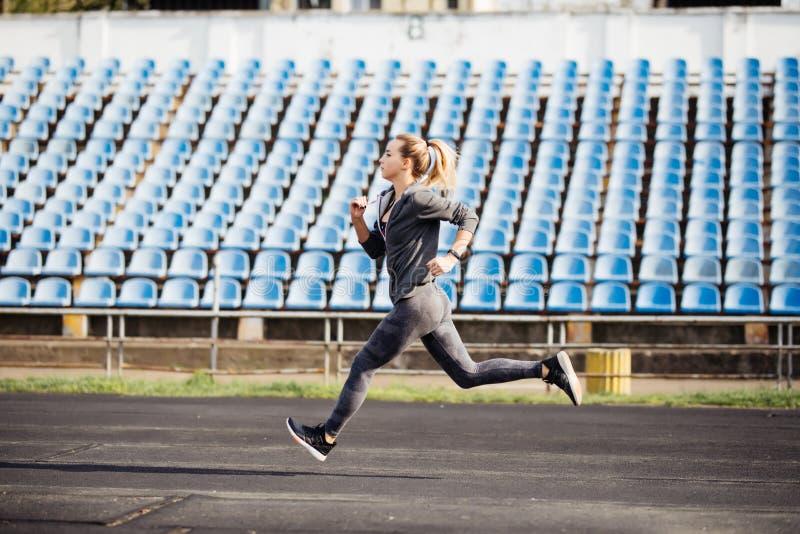 Mulher nova da aptidão que corre durante a manhã ensolarada na trilha do estádio imagem de stock royalty free