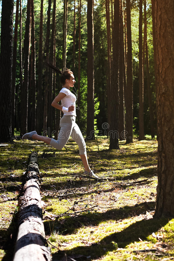 Mulher nova da aptidão que corre e que salta sobre logs quando no treinamento exterior extremo da aptidão na floresta fotografia de stock