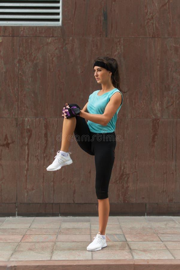 Mulher nova da aptidão que faz o exercício do aquecimento antes de correr esticando seu pé pelo joelho de execução ao estiramento imagens de stock
