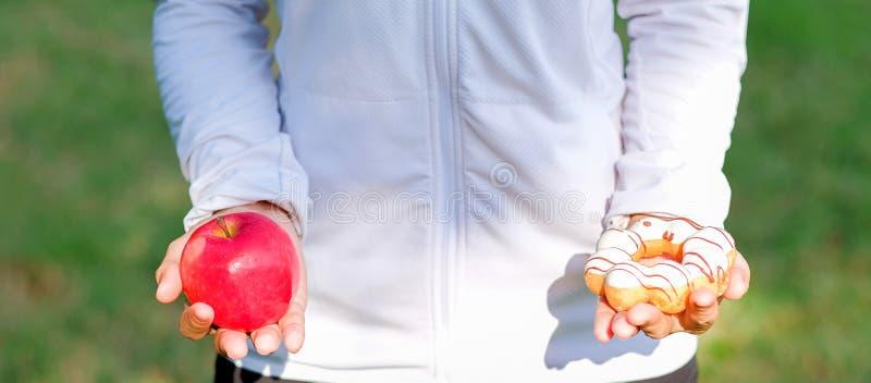 Mulher nova da aptidão que realiza nas mãos maçã e filhós vermelhas fotografia de stock royalty free