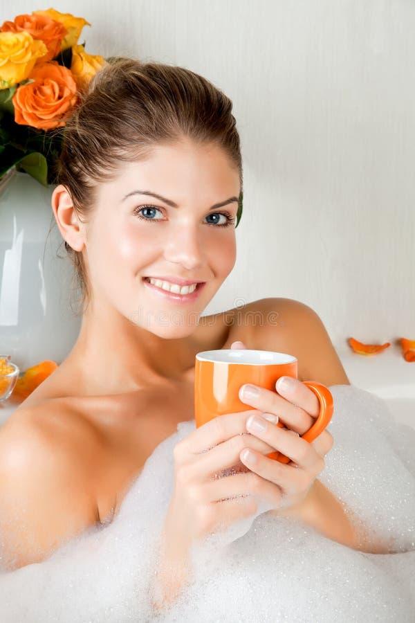 Mulher nova da beleza no banho que bebe o chá erval