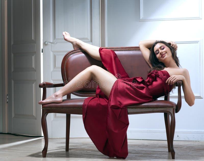 Mulher nova da beleza no sofá imagens de stock