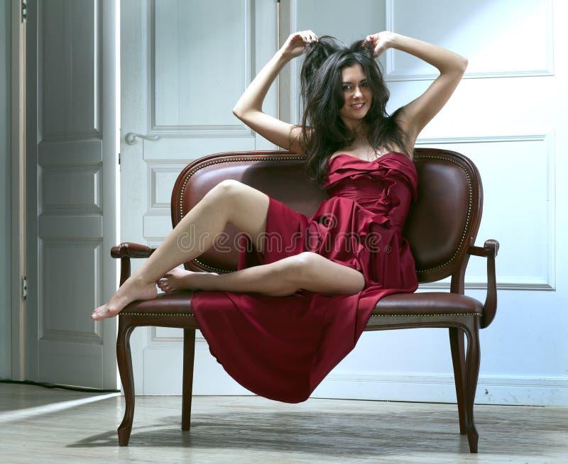 Mulher nova da beleza no sofá imagem de stock