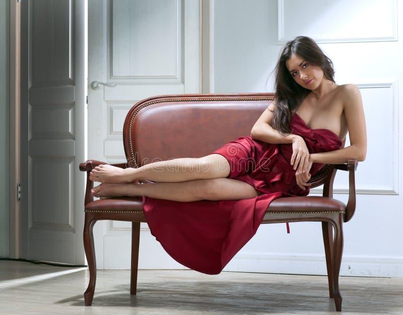 Mulher nova da beleza no sofá fotografia de stock royalty free