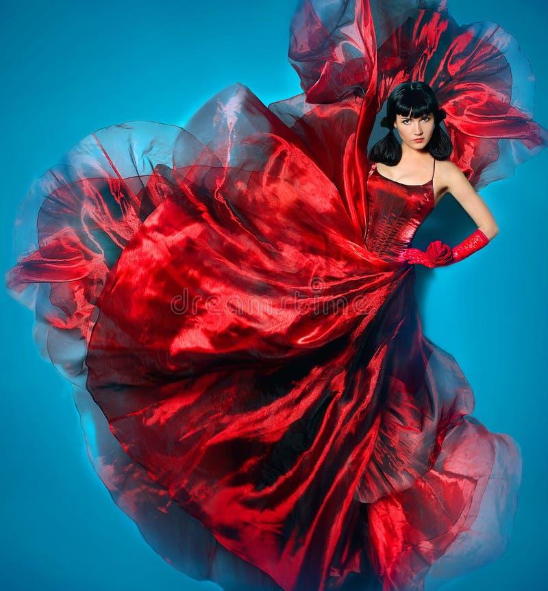 Mulher nova da beleza no vestido de ondulação vermelho do voo Dançarino no vestido de seda fotos de stock royalty free