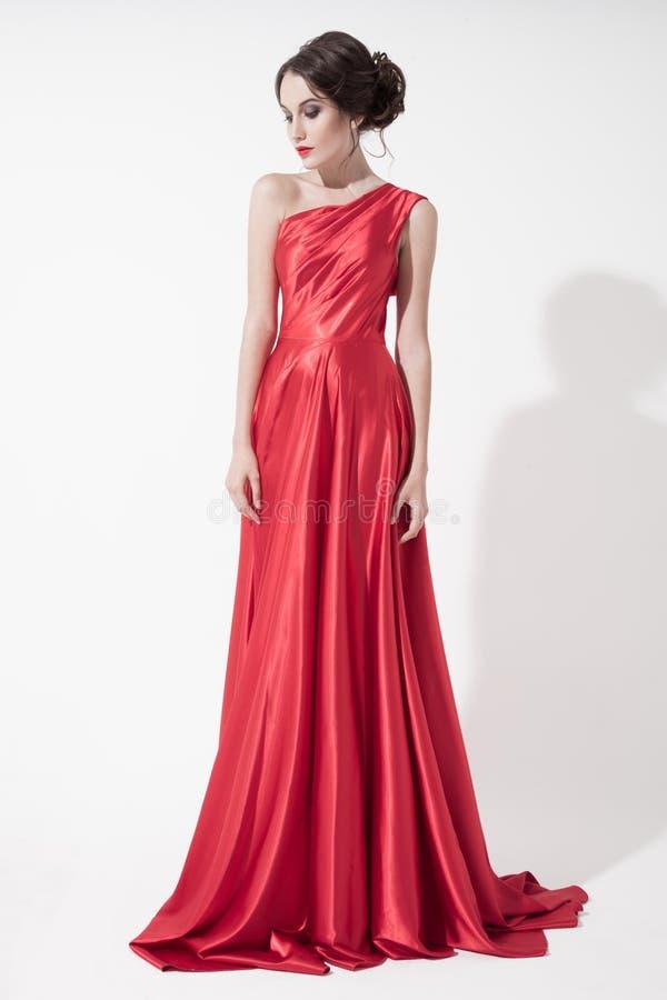 Mulher nova da beleza no vestido vermelho. Fundo branco. foto de stock