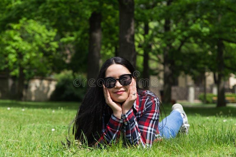 Mulher nova da beleza nos óculos de sol que encontram-se na grama imagem de stock