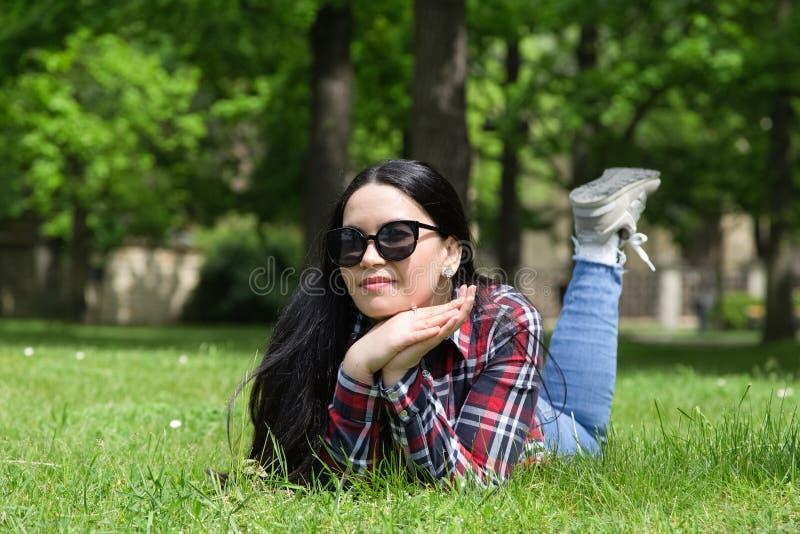 Mulher nova da beleza nos óculos de sol que encontram-se na grama imagem de stock royalty free