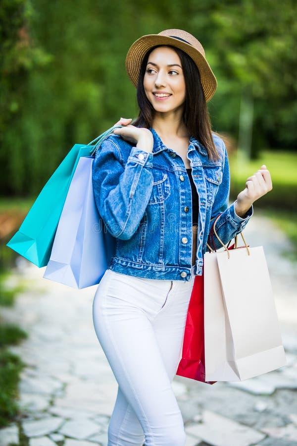 Mulher nova da beleza que guarda os sacos de compras que andam na paridade da cidade imagem de stock