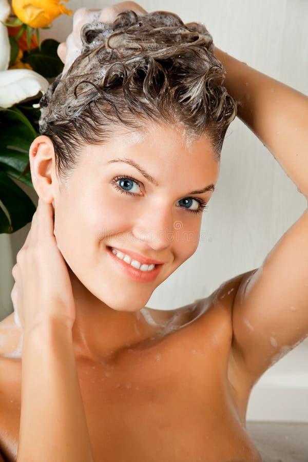 Mulher nova da beleza que lava seu cabelo fotografia de stock royalty free