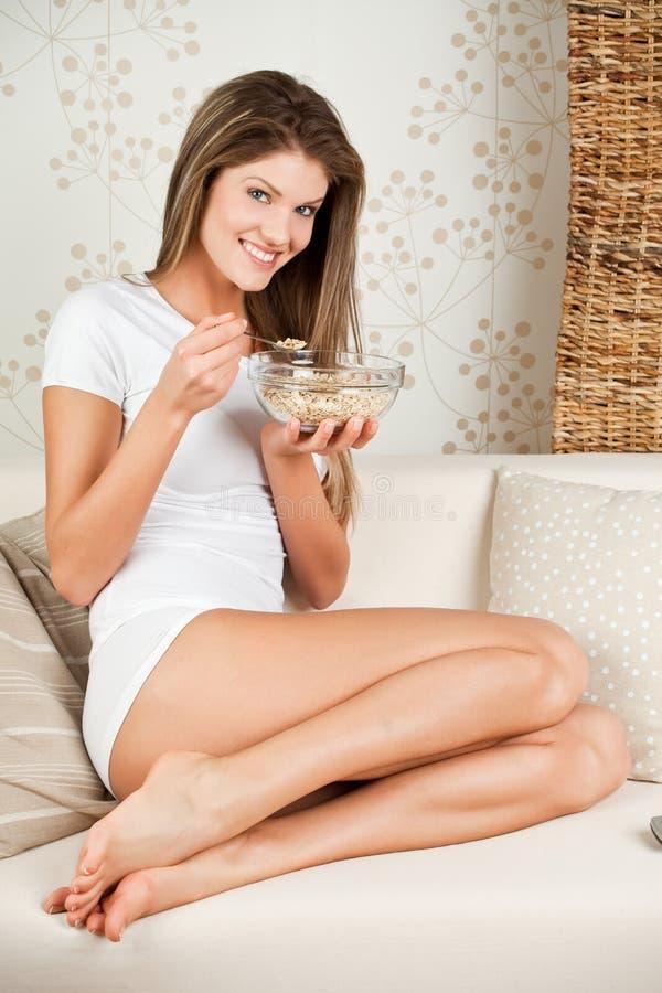 Download Mulher Nova Da Beleza Que Senta-se No Sofá E Que Come O Milho Imagem de Stock - Imagem de fêmea, cholesterol: 12802917