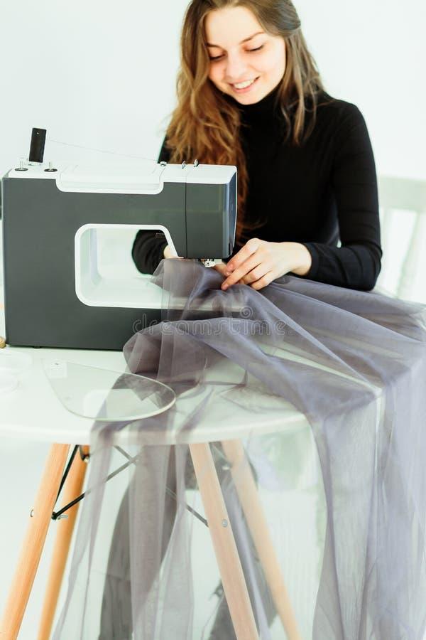 A mulher nova da costureira costura a roupa na m?quina de costura imagens de stock royalty free