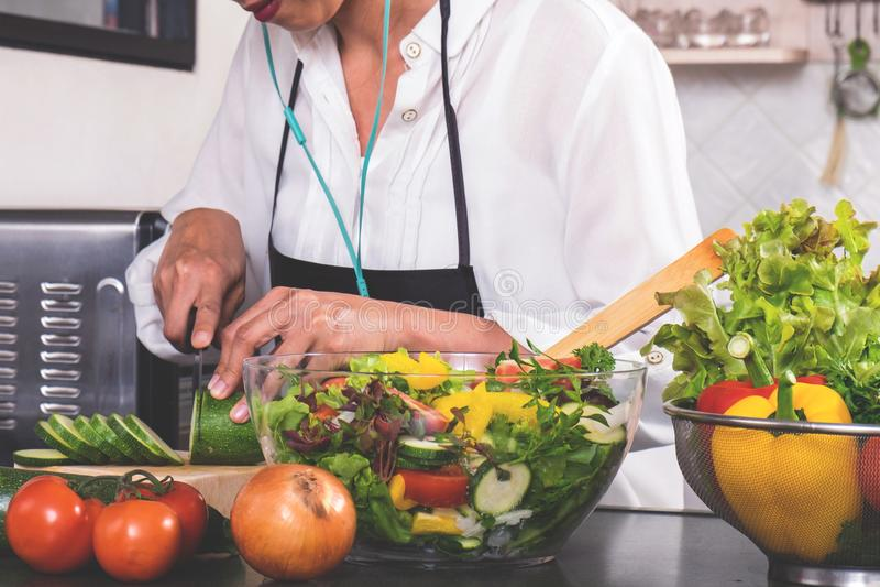 Mulher nova da felicidade que cozinha a salada dos vegetais na cozinha imagens de stock
