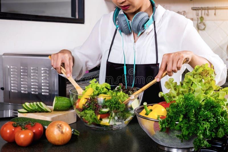 Mulher nova da felicidade que cozinha a salada na cozinha, H dos vegetais foto de stock