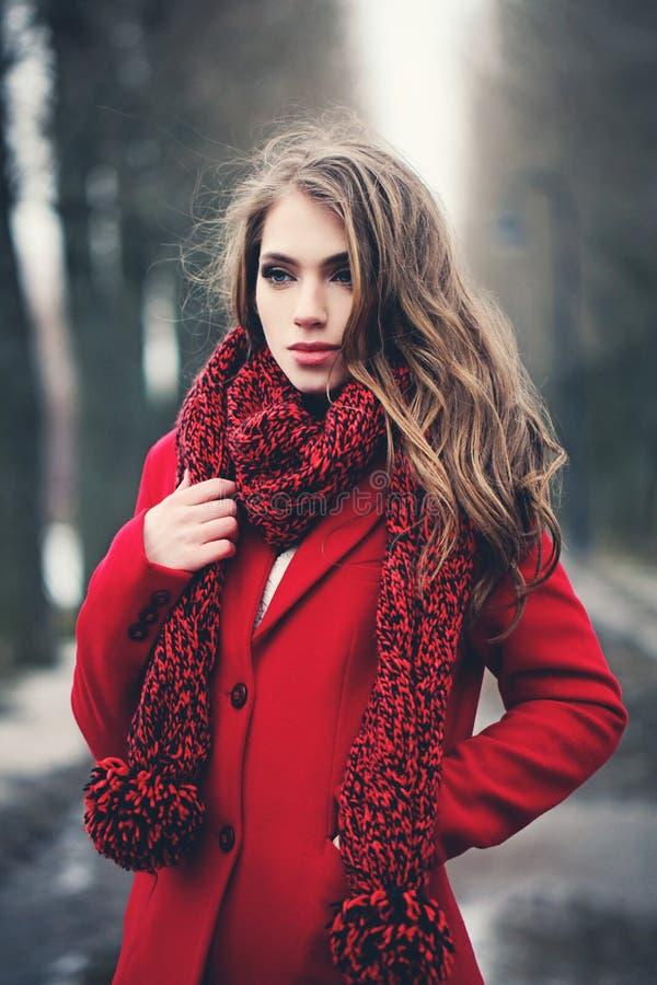 Mulher nova da forma no revestimento vermelho no parque fotos de stock