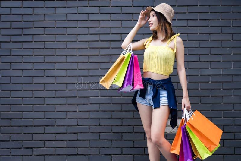 Mulher nova da forma que guarda os sacos de compras que olham o isolador da câmera fotos de stock royalty free