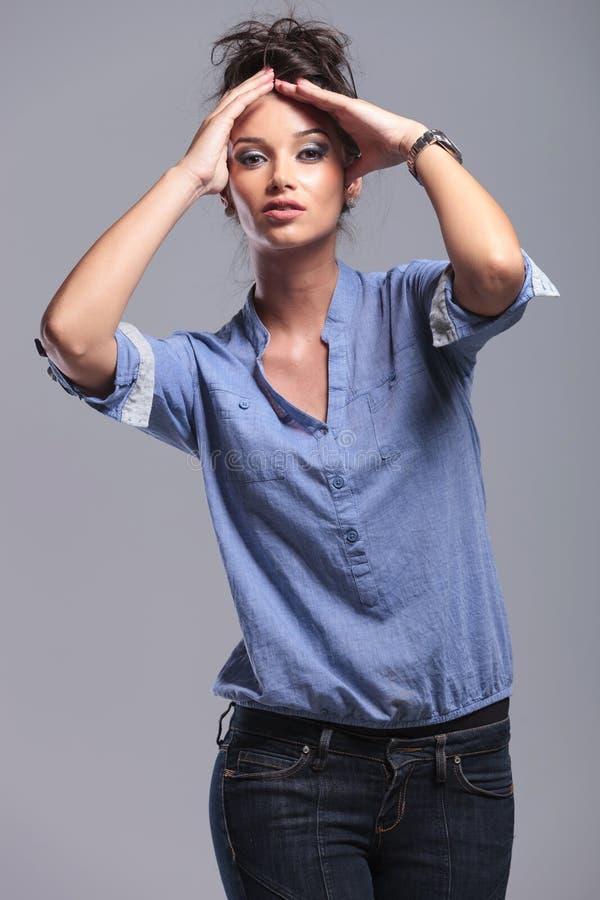 Mulher nova da forma que guarda suas mãos em sua cabeça fotos de stock royalty free