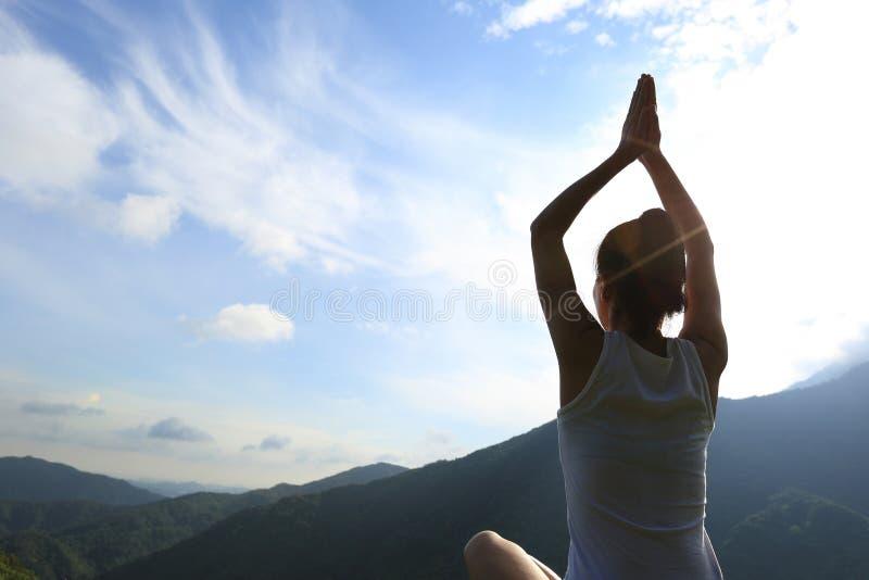 Mulher nova da ioga na montanha do nascer do sol imagens de stock