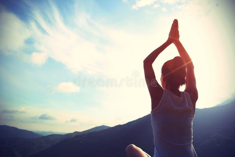 Mulher nova da ioga na montanha do nascer do sol fotografia de stock