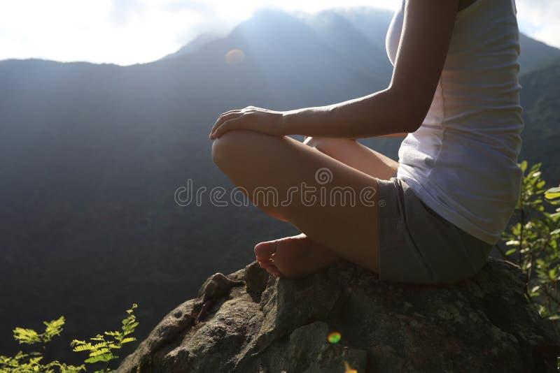 Mulher nova da ioga na montanha do nascer do sol imagem de stock royalty free