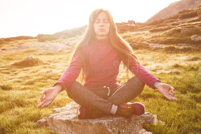 Mulher nova da ioga no nascer do sol fotografia de stock