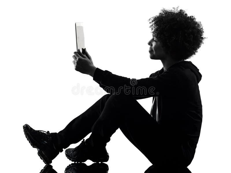 A mulher nova da menina do adolescente que usa a silhueta digital da sombra da tabuleta isolou-se imagem de stock royalty free