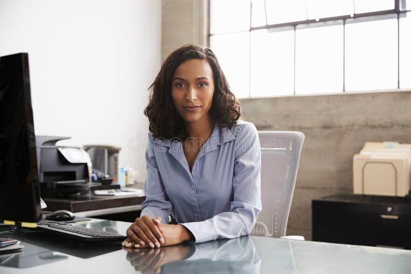 Mulher nova da raça misturada na mesa de escritório que olha à câmera imagens de stock