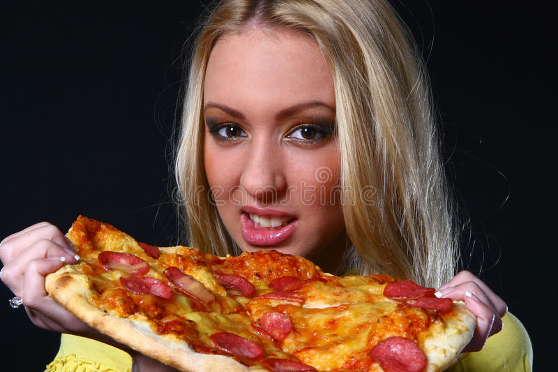 Mulher nova de Beautifull que come a pizza foto de stock