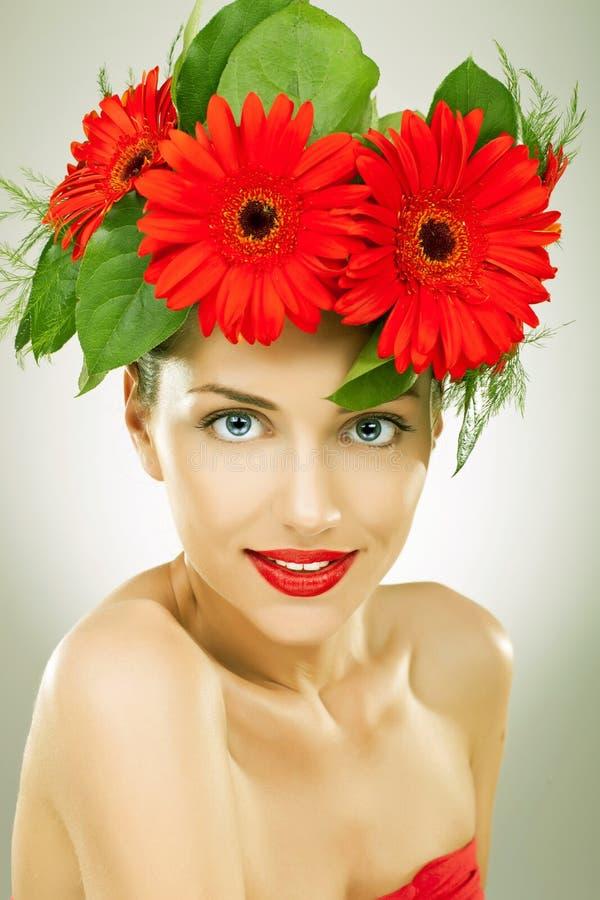 Mulher nova de Gracefull com as flores vermelhas em seu cabelo fotografia de stock royalty free