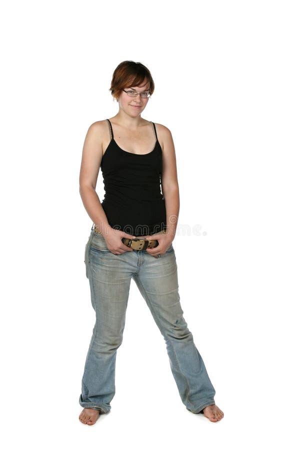 Mulher nova de pé desencapado em calças de brim desvanecidas fotografia de stock royalty free